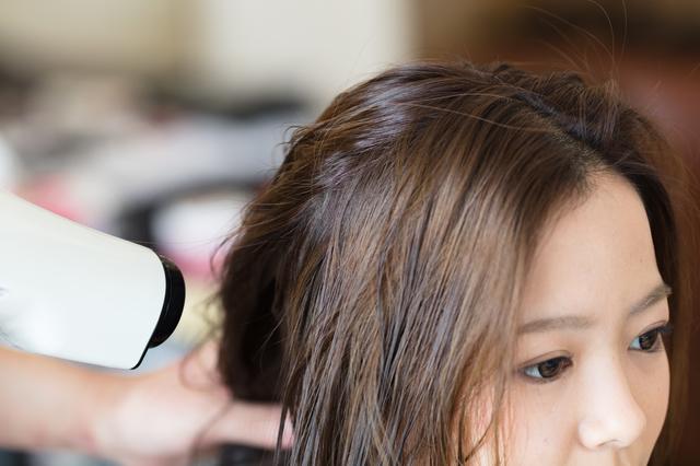 頭皮から髪を乾かす女性